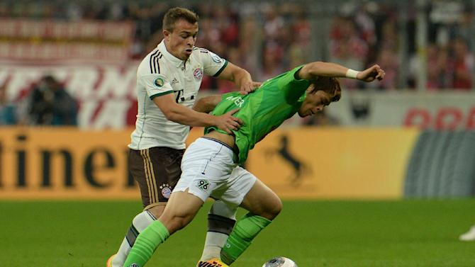 Munich's Xherdan Shaqiri of Switzerland, left, challenges for the ball with Hannover's Hiroki Sakai of Japan during the German soccer cup second round match between FC Bayern Munich and Hannover 96 , in Munich, southern Germany, Wednesday, Sept. 25, 2013