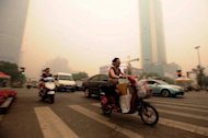 Chinese motorists wear masks as they make their way along a busy intersection in Wuhan on June 11. Wuhan was blanketed by thick yellowish cloud Monday, raising fears of pollution among its nine million inhabitants, residents told AFP. Witnesses said the haze appeared suddenly in the morning, and residents rushed to put on face masks