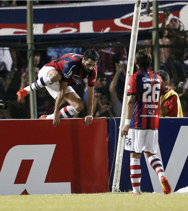 Guiza of Paraguay's Cerro Porteno jumps over the fencing as he celebrates a goal with teammate Romero during their Copa Libertadores soccer match against Colombia's Deportivo Cali in Asuncion
