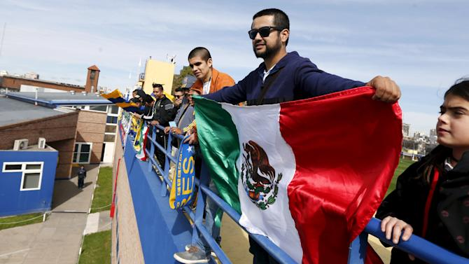 A supporter of Mexico's soccer team Tigres displays a Mexican national flag during the team's training session ahead in Buenos Aires