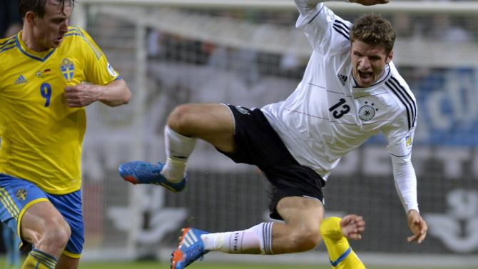 Germany's Thomas Muller, top, jumps over Sweden's Martin Olsson as Sweden's Kim Kallstrom, left, looks on during the 2014 World Cup group C qualifying soccer match between Sweden and Germany at Friends Arena in Stockholm, Sweden, on Tuesday Oct. 15, 2013