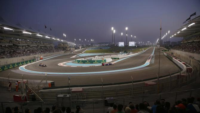 The crowd watch Red Bull Formula One drivers Vettel of Germany and Webber of Australia drive during the qualifying session of the Abu Dhabi F1 Grand Prix at the Yas Marina circuit on Yas Island