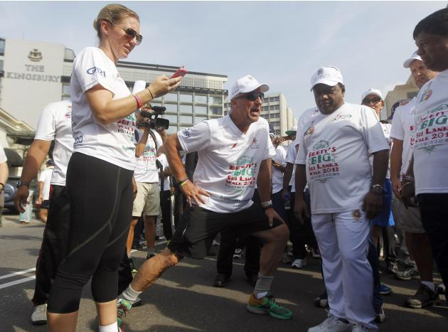 Former England cricket captain Botham stretches during his charity walk in Colombo