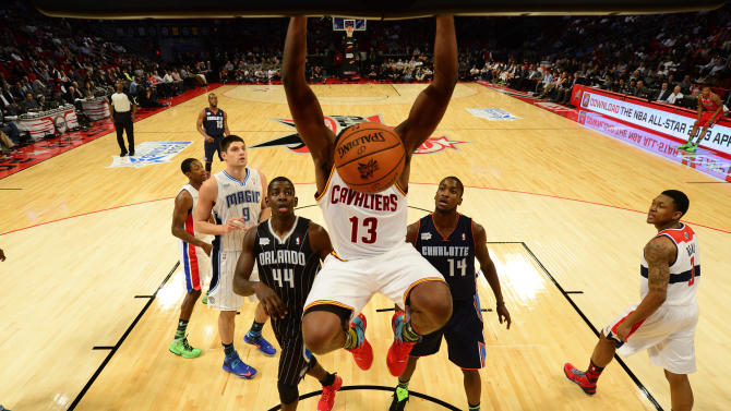 Cavaliers Thompson hangs on the rim after a dunk during the first half of the NBA BBVA Rising Star Challenge basketball game in Houston