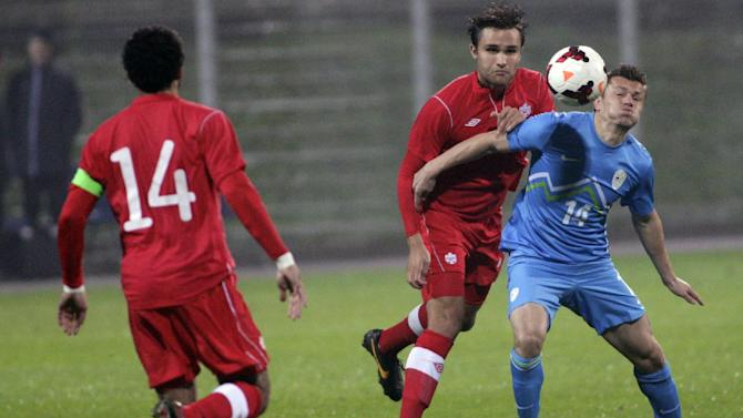 Slovenia's Zlatko Dedic, left, is challenged by Canada's Adam Straith , center as Canada's Dwayne De Rosario watches during a friendly soccer match between Slovenia and Canada, in Celje, Slovenia, Tuesday, Nov. 19, 2013