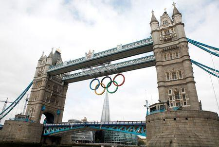 The Olympic Rings are seen hanging from Tower Bridge after being lowered into position for display from the walkways in central London