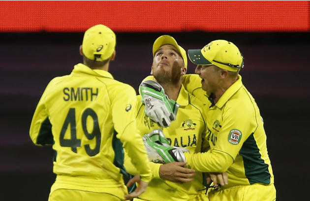 Australian cricketers congratulate teammate Aaron Finch, center, for the wicket of Afghanistan's Nawroz Mangal during their Cricket World Cup Pool A match in Perth, Australia, Wednesday, March 4, 2015