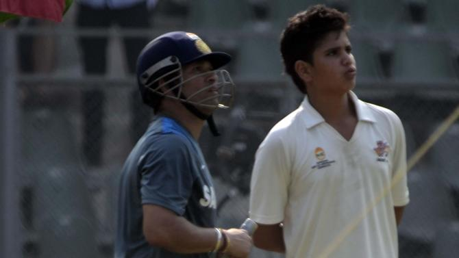 Indian cricketer Sachin Tendulkar with his son Arjun Tendulkar during practice session ahead of his 200th and last Test match at Wankhede stadium in Mumbai on Nov.12, 2013. (Photo: Sandeep Mahankaal/IANS)