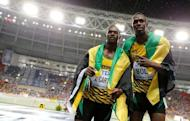 First placed Usain Bolt (R) of Jamaica poses with his compatriot third placed Nesta Carter after competing in the men's 100 metres final during the IAAF World Athletics Championships at the Luzhniki stadium in Moscow August 11, 2013. REUTERS/Dominic Ebenbichler/Files