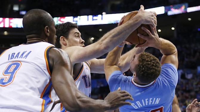 Oklahoma City Thunder forward Nick Collison (4) tries to take the ball away from Los Angeles Clippers forward Blake Griffin (32) in the first quarter of an NBA basketball game, Sunday, Feb. 23, 2014, in Oklahoma City. Thunder forward Serge Ibaka (9) is at right. (AP Photo/Sue Ogrocki)