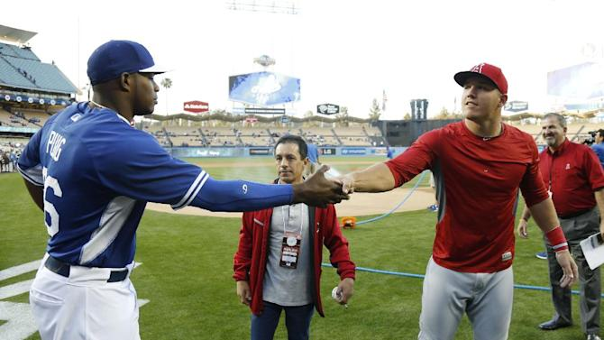 Los Angeles Dodgers' Yasiel Puig, left, shakes hands with Los Angeles Angels' Mike Trout, right, after they talked with jockey Victor Espinoza, center, before Espinoza threw out the first pitch for an exhibition baseball game in Los Angeles, Thursday, March 27, 2014