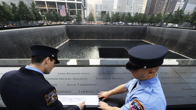 New York Fire Department firefighters Andrew Esposito (L) and his brother Michael Esposito make a rubbing of their father's nam at the 9/11 Memorial during ceremonies marking the 12th anniversary of the 9/11 attacks in New York