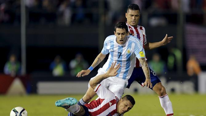 Paraguay's Ortiz falls on the ground under pressure of Argentina's Di Maria during their 2018 World Cup qualifying soccer match at the Defensores del Chaco stadium in Asuncion