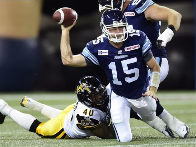 Toronto Argonauts quarterback Ricky Ray, right, tries to get a pass away as he's sacked by Hamilton Tiger-Cats defensive end Eric Norwood during first half CFL action in Toronto on Friday, October