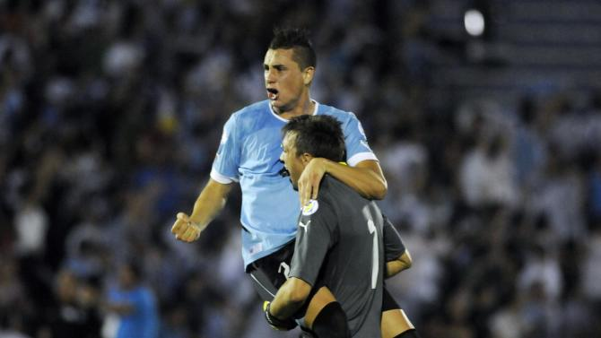 Uruguay's Muslera celebrates with Gimenez after their team scored against Colombia during their 2014 World Cup qualifying soccer match in Montevideo
