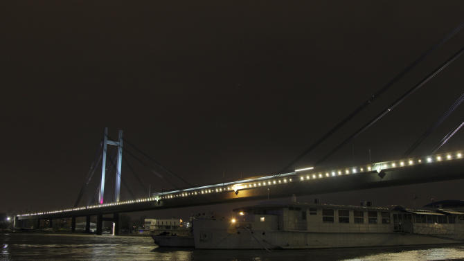 "In this combo of two photos the illuminated ""New railroad bridge"" over Sava river, top, and a picture of the bridge with most of its lights turned off, are seen in Belgrade, Serbia, Saturday, March 23, 2013. Organised by the World Wide Fund for Nature, earth hour is observed every year to create awareness about conservation of energy and climate change. Around the world, people and organisations will be turning their lights off from 8:30 to 9:30 pm local time. (AP Photo/Darko Vojinovic)"