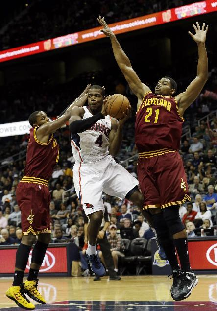 Atlanta Hawks power forward Paul Millsap (4) drives between Cleveland Cavaliers' C.J. Miles, lfet, and Andrew Bynum (21) in the first half of an NBA  basketball game Friday, Dec. 6, 2013, in Atlanta