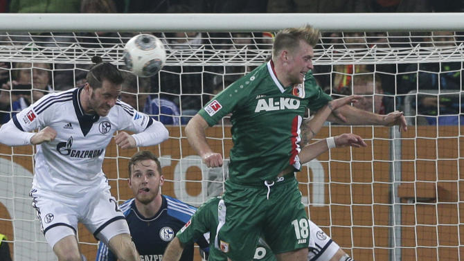 Schalke's Tim Hoogland, left, and Augsburg's Jan-Ingwer Callsen-Bracker challenge for the ball during the German first division Bundesliga soccer match between FC Augsburg and FC Schalke 04, in Augsburg, southern Germany, Friday, March 14, 2014