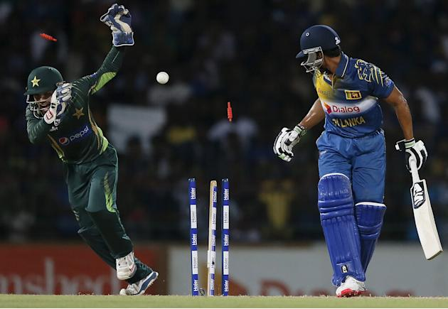 Pakistan's wicket Rizwan tries to cover his face from bails as Sri Lanka's de Silva is bowled out by Pakistan's captain Afridi during their second Twenty 20 cricket match in Colombo