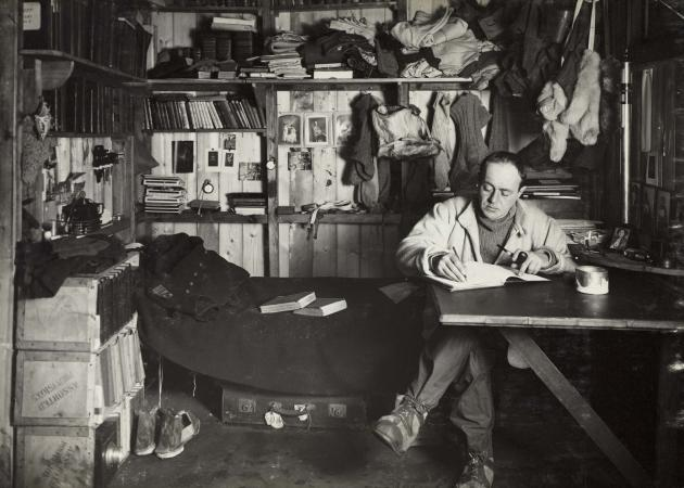 Scott writing in his area of the expedition hut, Scott's cubicle. ©H Ponting photograph, Pennell collection Canterbury Museum NZ, 1975.289.35