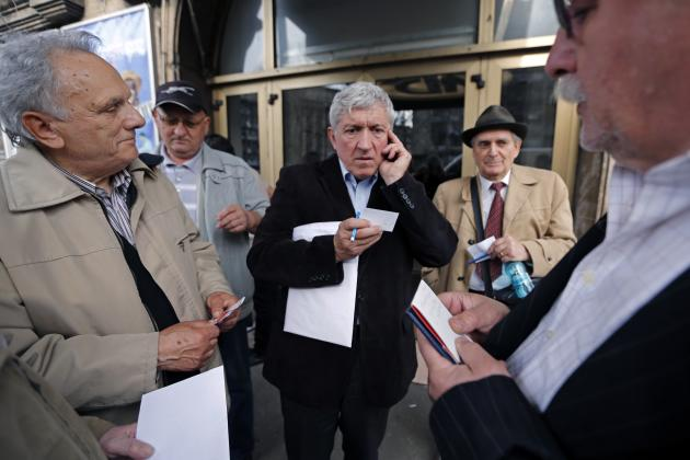 Romanian actor and former senior member of National Liberal Party, Mircea Diaconu talks on the phone as supporters wait for him to sign autographs, outside the Nottara theatre in Bucharest