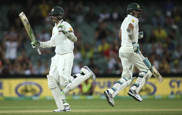 Australia's Peter Siddle, left, celebrates hitting the winning runs as he passes teammate Mitchell Starc during their cricket test against New Zealand in Adelaide, Australia, Sunday, Nov. 29, 2015