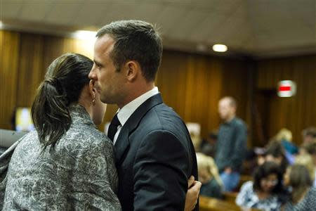 Olympic and Paralympic track star Oscar Pistorius speaks to his sister Aimee Pistorius during the fifth day of his trial for the murder of his girlfriend Reeva Steenkamp at the North Gauteng High Court in Pretoria
