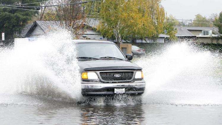 Water flies as a vehicle drives through a flooded street in Sacramento, Calif., Friday, Nov. 30, 2012. The second in a series of storms slammed Northern California on Friday as heavy rain and strong winds knocked out power, tied up traffic and caused flooding along some stretches. (AP Photo/Rich Pedroncelli)
