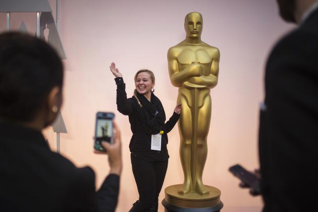 Hegedus, a talent production assistant, poses with an Oscar statue on the red carpet outside the Dolby Theatre in Hollywood, hours before arrivals for the Academy Awards in Los Angeles, California