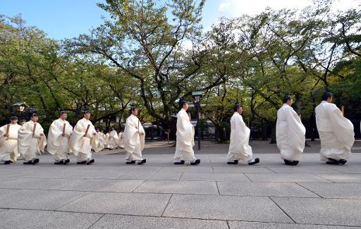 "Shinto priests walk to the main shrine as they administer a Shinto rite ""Kiyoharai"" on the first day of the four-day autumn festival at the Yasukuni shrine in Tokyo on October 17, 2013"