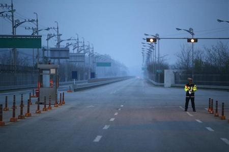 A South Korean police officer stands guard on an empty road connecting the Kaesong Industrial Complex (KIC) inside the North Korean border with the South's CIQ (Customs, Immigration and Quarantine), just south of the demilitarized zone separating the two Koreas, in Paju, north of Seoul May 3, 2013. REUTERS/Kim Hong-Ji