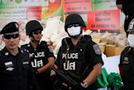 This file photo shows Thai police officers keeping watch in front of seized drugs during the 41th Destruction of Confiscated Narcotics ceremony in Ayutthaya province, on June 29. Eight suspected drug dealers were killed on Monday in a clash with Thai security forces who seized weapons and a large amount of illegal amphetamines
