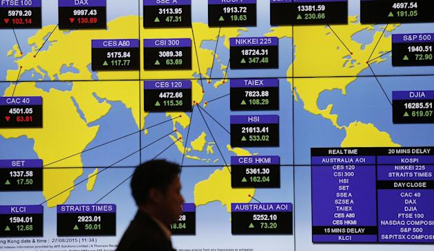 FILE - In this Aug. 27, 2015 file photo, a man walks past a bank's electronic board showing the share index around the world at Hong Kong Stock Exchange. Investors have yanked $40 billion from eme