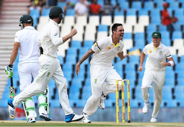 Australia's bowler Mitchell Johnson, second from right, with teammates reacts after dismissing South Africa's batsman Faf du Plessis, left, for 3 runs on the second day of their their cricket