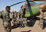 French soldiers of the 5th Combat Helicopter Regiment stand with their equipment in front of a PUMA helicopter on January 19, 2013 at the 101st airbase near Bamako. West African leaders Saturday urged more global involvement and funding as they met to speed up the deployment of regional troops in Mali and boost a French-backed offensive to halt an Islamist onslaught