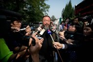 Chinese artist Ai Weiwei (C) talks to the foreign media outside a court in Beijing. A Beijing court has rejected Ai's appeal against a $2.4 million fine for tax evasion that he calls politically motivated