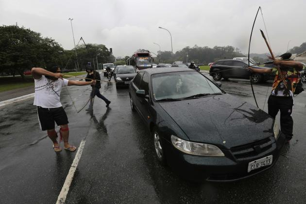 Guarani Indians use their bows and arrows to stop drivers from passing a roadblock in Sao Paulo
