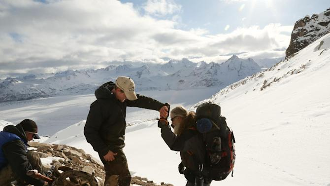 "In this 2012 photo released by National Geographic Channels and Brian Catalina Entertainment, Dallas Seavey, center left, high-fives Willi Prittie in the Tordrillo Mountains in Alaska. Seavey, who became the youngest Iditarod champion ever when he won the race in 2012, is among eight mushers or outdoor adventurers featured in the latest reality show set in Alaska. ""Ultimate Survival Alaska"" premieres Sunday on NatGeoTV. (AP Photo/Brian Catalina Entertainment, Kyle Wheeler)"