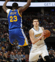 Denver Nuggets forward Nikola Jokic, right, of Serbia, slips past Golden State Warriors forward Draymond Green to take a shot in the second half of an NBA basketball game Monday, Feb. 13, 201, in Denver. The Nuggets won 132-110. (AP Photo/David Zalubowski)