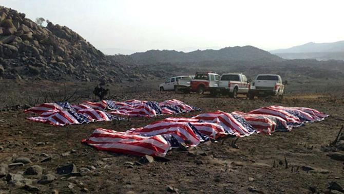 This photo that appeared anonymously on Facebook on Thursday, July 4, 2013, shows what officials confirmed to The Associated Press, as the 19 dead firefighters draped in American flags by Yavapai County Sheriff Scott Mascher, shortly after they were found dead near Prescott, Ariz., on June 30, 2013. Several media outlets, including the Arizona Republic and USA Today, published the photo on Friday, July 5, 2013. Nineteen members of the Granite Mountain Hotshot crew died Sunday, June 30, 2013 fighting the Yarnell Hills Fire, about 40 miles southwest of Prescott. (AP Photo) AP PROVIDES ACCESS TO THIS HANDOUT PHOTO TO BE USED SOLELY TO ILLUSTRATE NEWS REPORTING OR COMMENTARY ON THE FACTS OR EVENTS DEPICTED IN THIS IMAGE. ONE TIME USE ONLY.