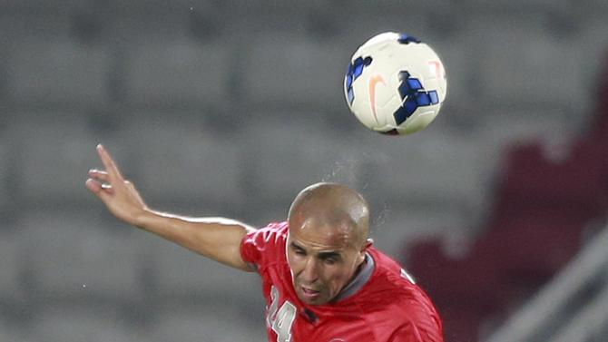 Bougherra of Qatar's Lekhwiya fights for the ball with Fatadi of Bahrain's Al-Hidd during their AFC Champions League match in Doha