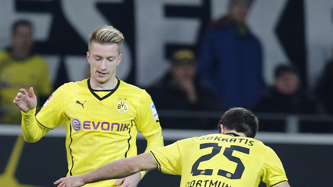 Dortmund's Marco Reus, left, Dortmund's Sokratis of Greece, right, and Berlin's Sami Allagui of Tunesia challenge for the ball during the German first division Bundesliga soccer match between Borussia Dortmund and Hertha BSC Berlin in Dortmund , Germany, Saturday, Dec. 21, 2013