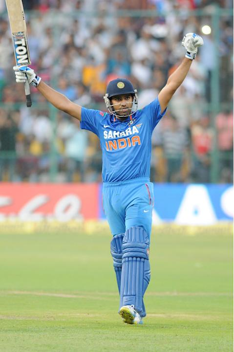 Indian player Rohit Sharma lifts his bat to celebrate his century during the 7th ODI between India and Australia played at Chinnaswamy Stadium in Bangalore on Nov.2, 2013. (Photo: IANS)