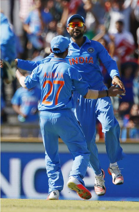 India's Ajinkya Rahane and Virat Kohli celebrate the wicket of West Indies batsman Marlon Samuels, run out by Mohit Sharma during their Cricket World Cup match in Perth
