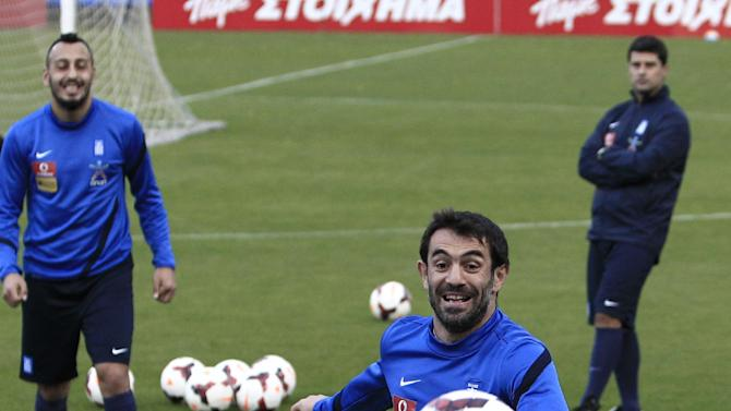 Greek national soccer team captain Giorgos Karagounis, center, runs for the ball during a training session in Athens, Thursday, Nov. 14, 2013. The Greek national soccer team will face Romania for a World Cup qualifying playoff on Friday