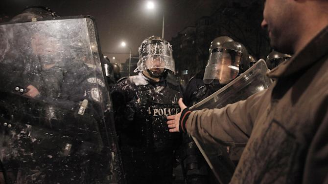 A protester reaches his hand out to a  riot police officer after clashes with demonstrators in a protest against high electricity prices in Sofia, on late Tuesday, Feb. 19, 2013.  Bulgaria's prime minister announced on Tuesday that the license held by a Czech company for power distribution in parts of the Balkan country will be revoked following protests against high electricity prices. (AP Photo/Valentina Petrova)