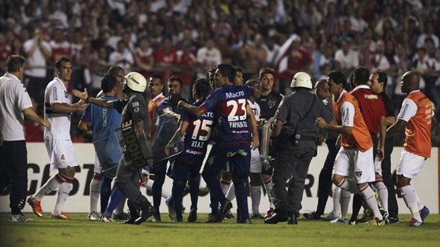 Players of Brazil's Sao Paulo (in white) argue with players of Argentina's Tigre at the end of the first half of their Copa Sudamericana final second ...
