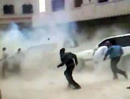 An image grab from video footage uploaded on Youtube allegedly shows Syrians running for cover as a roadside bomb explodes in front of a UN observers convoy in Khan Sheikhun between the cities of Hama and Idlib, without causing any injuries, according to UN officials