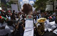 An activist wearing a beaded bracelet in the colors of the Kenyan flag holds his fist in the air as he and medical staff protest the detention of union leaders, outside an appeal court in Nairobi, Kenya, Wednesday, Feb. 15, 2017. A Kenyan court has released seven doctors who are officials in the medics' union and who were jailed earlier this week for not calling off a strike by doctors working in public institutions. (AP Photo/Ben Curtis)