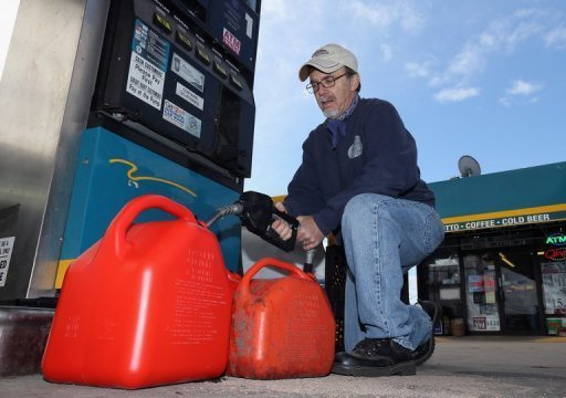 A man fills up gas containers in New York on November 5. Oil prices closed higher Friday as investors grew more optimistic about an improvement in Europe's economic situation and took advantage of a weaker dollar.